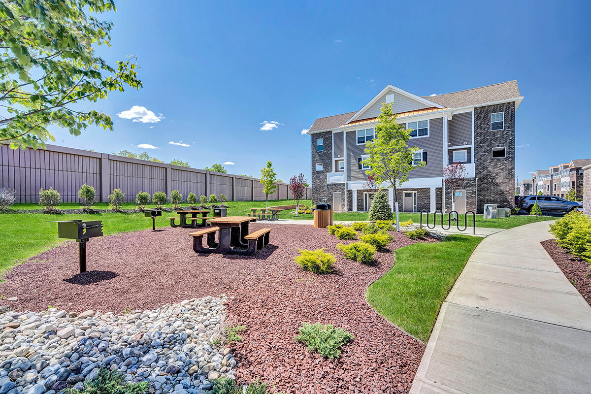 River Links apartments exterior view with picnic tables and grills.