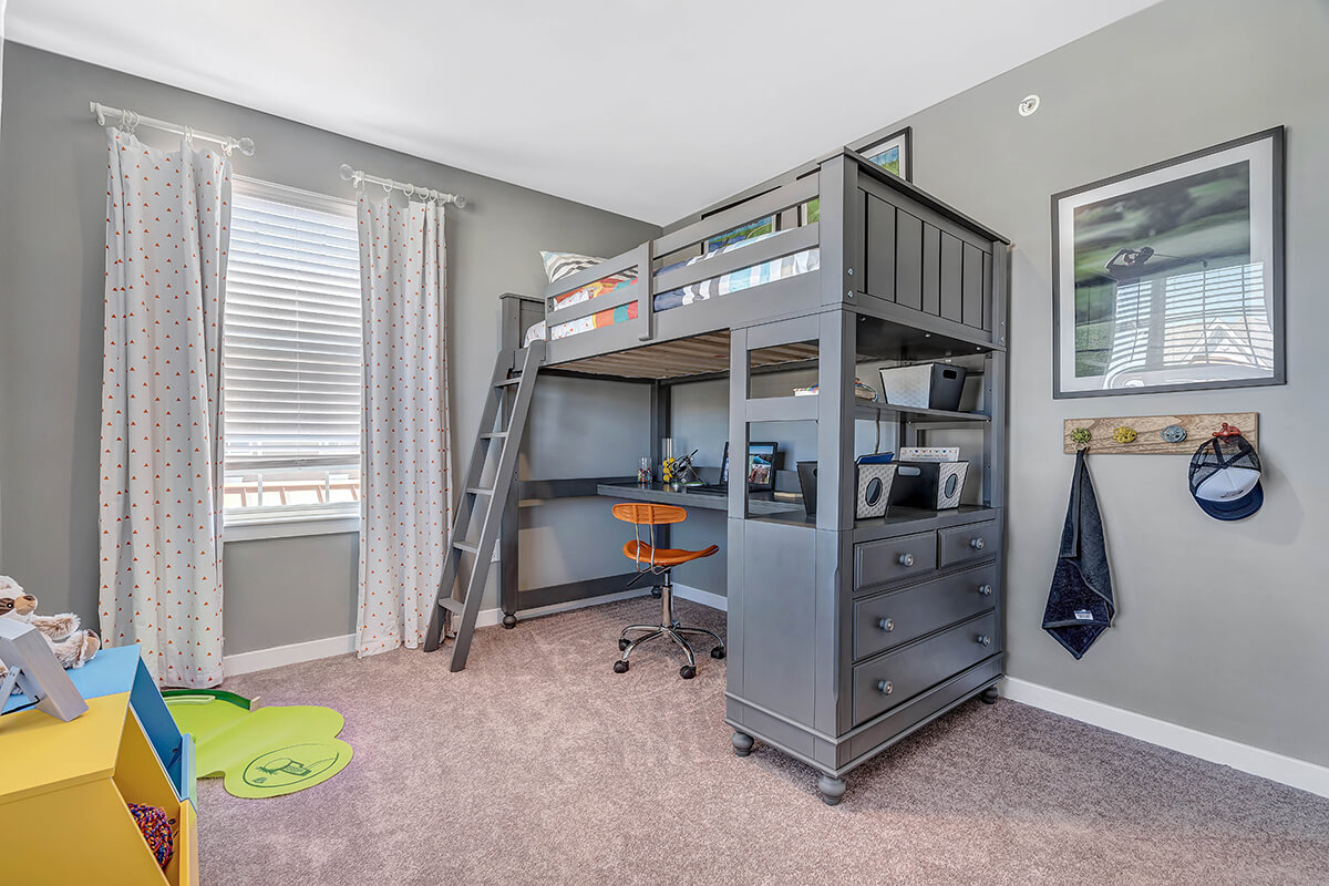 Bedroom with a desk under a bunkbed in a River Links apartment.